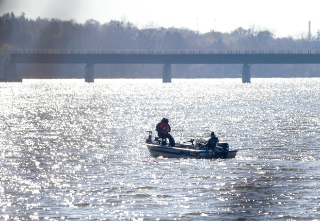 Two men fish on the Fox River in Green Bay.