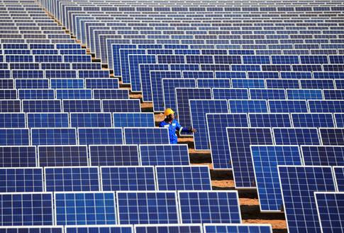A worker walks between solar panels at Centragrid power plant in Nyabira, Zimbabwe, June 23, 2020. REUTERS/Philimon Bulawayo - RC2XEH95PCV2