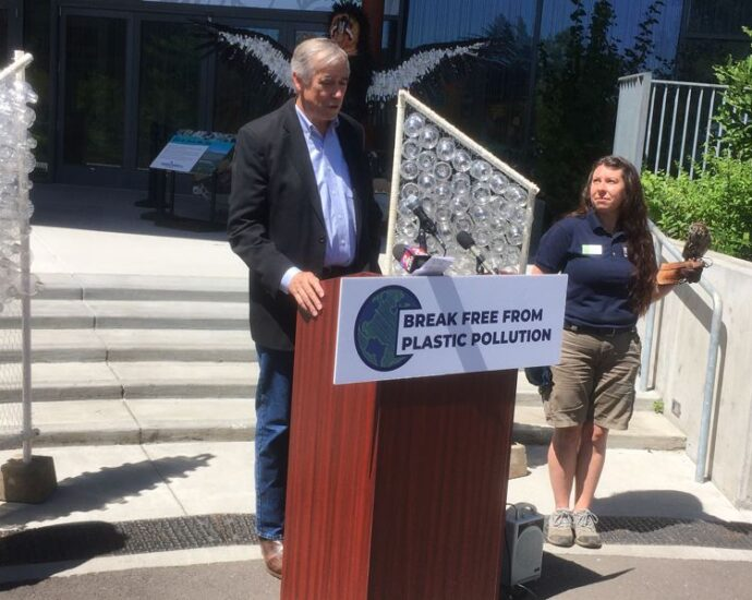 PMG PHOTO: PETER WONG - U.S. Sen. Jeff Merkley, D-Ore., speaks at the Oregon Zoo about his federal legislation to require producers of plastic packaging to share in the cost of reusing or recycling their materials. At right at the Friday, July 23 event is Bree Boothe, a zoo employee; in her left hand is Pinecone, a rescued Western screech owl. Displays of single-use plastic water bottles flank Merkley on both sides; the zoo discontinued their use three years ago.