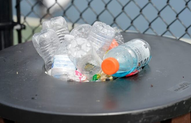 Plastic bottles overflow from a trash can at pickle ball courts in Mashpee.