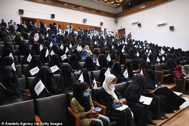 The Taliban has barred women from attending classes or working at Kabul University 'until an Islamic environment is created' (pictured, women attend a pro-Taliban program at Kabul University on September 11)