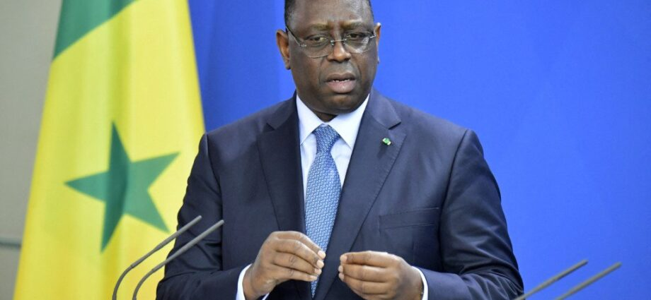 Senegalese President Macky Sall in front of his nation's flag.