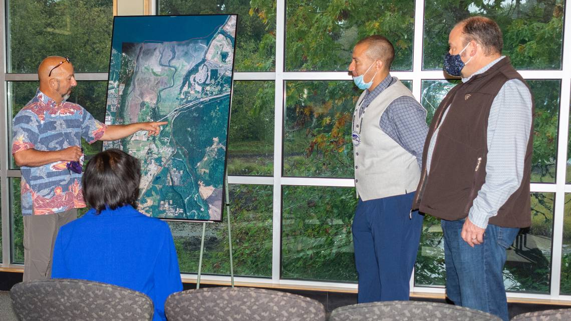 Nisqually Department of Natural Resources Director David Troutt, left, points to a map to discuss concerns for watershed protection and salmon recovery with White House Council on Environmental Quality Chair Brenda Mallory at a meeting with the council and Tribal leaders Tuesday, Oct. 5, at the Billy Frank Jr. Nisqually National Wildlife Refuge northeast of Olympia. Joined by Nisqually Indian Tribe Chairman Willie Frank III, middle, and Tribal Treasurer David Iyall, right, the team shared with Mallory the multiple ways their Tribe and others are mitigating the effects of climate change.